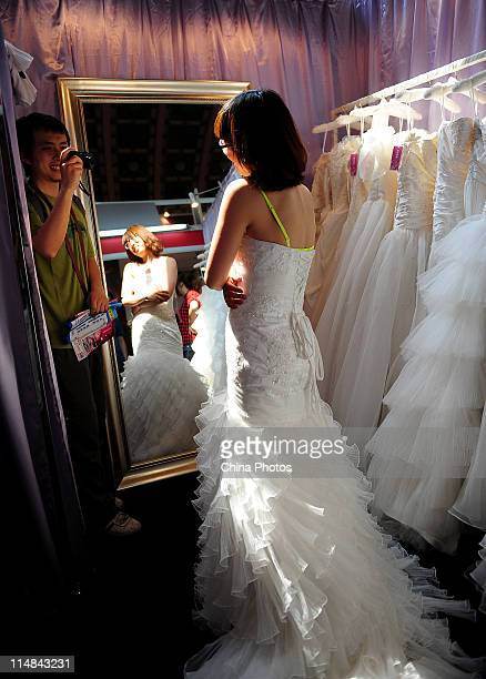 A woman tries on a wedding dress at the 2011 China Summer Wedding Expo at the Beijing Exhibition Center on May 27 2011 in Beijing China Hundreds of...