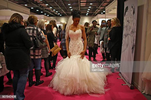 A woman tries on a wedding dress at the London Wedding Show at ExCel on January 30 2016 in London England The show advertises numerous businesses...
