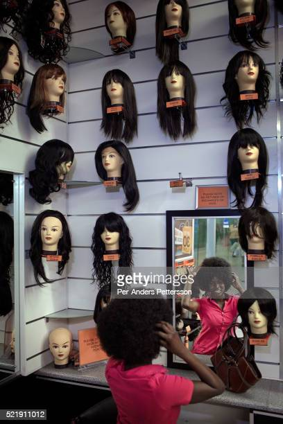 A woman tries on an Afro wig hair piece in a shop on October 5 2012 at Maponya shopping Mall Soweto South Africa Maponya is one of several new...