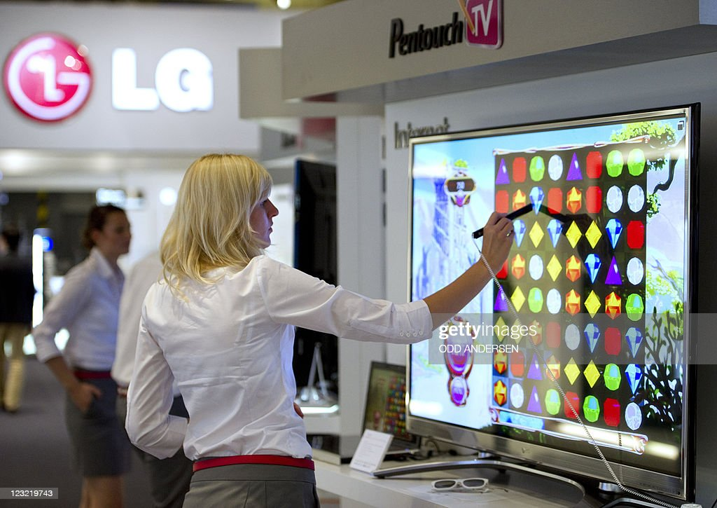A woman tries out a game on the touch screen TV at