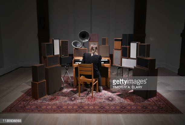 A woman tries out Janet Cardiff and George Bures Miller The Poetry Machine 2017 an interactive audio/mixedmedia installation including organ speakers...