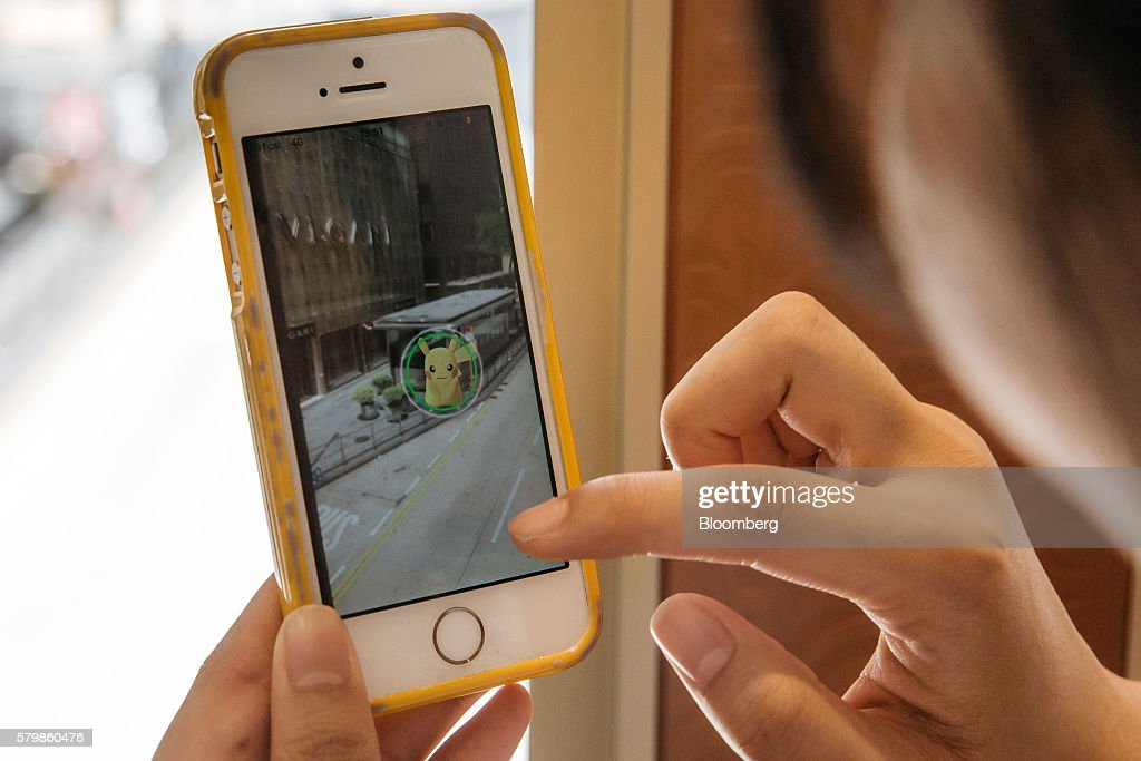 A woman tries to catch a Pikachu character while playing Nintendo Co.'s Pokemon Go augmented-reality game, developed by Niantic Inc., on her smartphone in Hong Kong, China, on Monday, July 25, 2016. After debuting in the U.S. earlier this month, Pokemon Go launched in Japan on Friday and became available in Hong Kong on Monday. Photographer: Anthony Kwan/Bloomberg via Getty Images