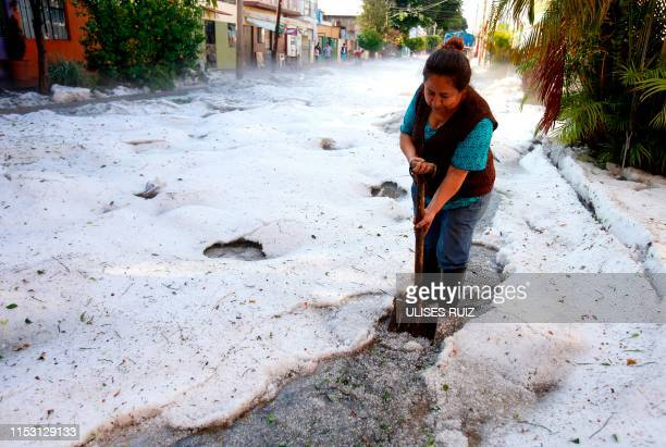 Woman tries to clear a street of Guadalajara, Jalisco State, Mexico, on June 30, 2019 after a hail storm fell in the area. - A freak hail storm on...