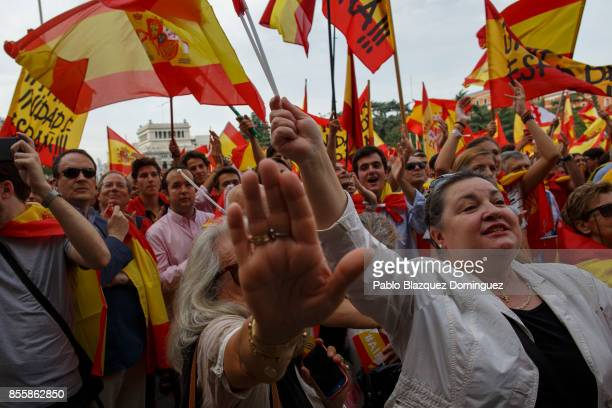 A woman tries to cover the photographers camera as antiseparatist demonstrators hold Spanish flags during a protest in support of Spain's unity ahead...