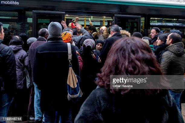 Woman tries to get through dozens of people trying to get into a public bus during the eighth day of a general strike on December 12, 2019 in Paris,...