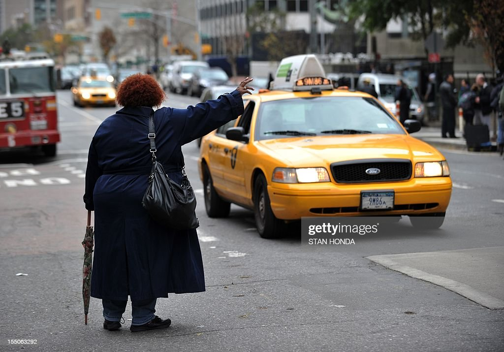 A woman tries to hail a taxi on First Avenue October 31, 2012 in New York. Yellow cabs were allowed to pick up multiple fares due to limited public transportation as a result of Hurricane Sandy. AFP PHOTO/Stan HONDA
