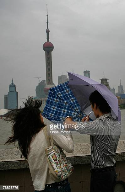 A woman tries to hold her umbrella in big wind triggered by typhoon Wipha at the Bund on September 19 2007 in Shanghai China About 1 million people...