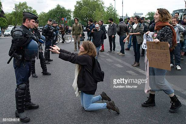 A woman tries to persuade a riot police officer to join the demonstrators in front of the National Assembly during the demonstration against the 'El...