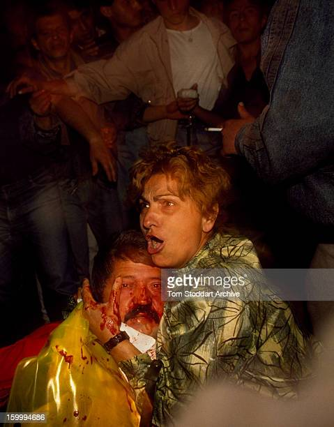 A woman tries to protect her husband a government supporter as he is attacked by an antiGovernment crowd in Bucharest Romania Months of unrest around...