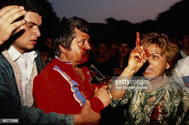 Woman tries to protect her husband, a government supporter, as he is attacked by an anti-Government crowd, possibly in Romania, circa 1990.