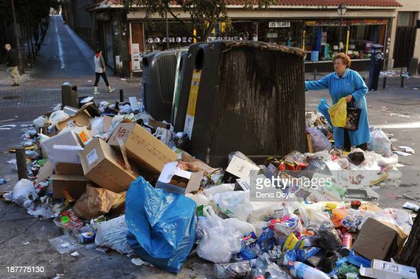 A woman tries to put her garbage into an overflowing bin in the city centre on November 12 2013 in Madrid Spain Street cleaners garbage collectors...