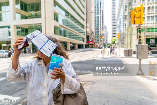 A woman tries to shield herself from the sun while walking in sweltering heat on July 1 2018 in Philadelphia Pennsylvania An excessive heat warning...