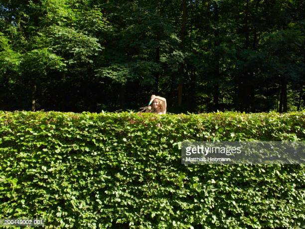 Woman trimming garden hedge with shears, smiling