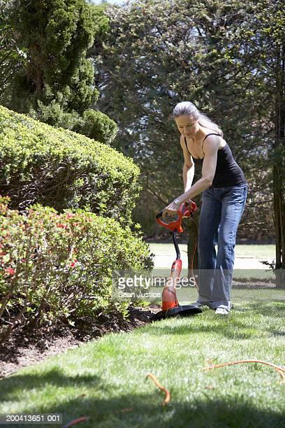 Woman trimming grass around hedge