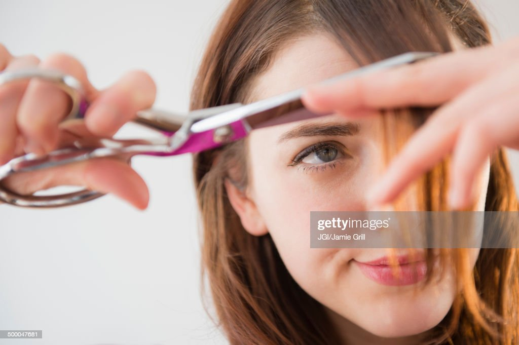 Woman trimming her bangs : Foto de stock