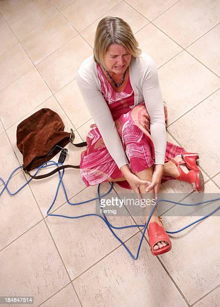 Frau darüber stolpert eine Elektrische Kabel
