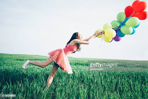 Woman try to hold balloons blown away by the wind