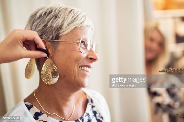woman trying earrings - earring stock pictures, royalty-free photos & images