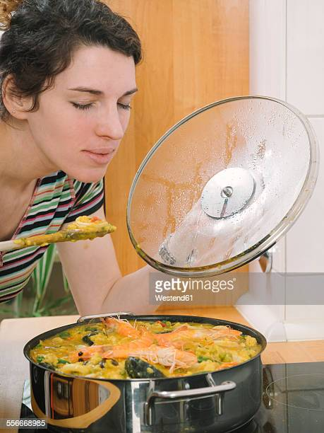 Woman trying freshly cooked paella