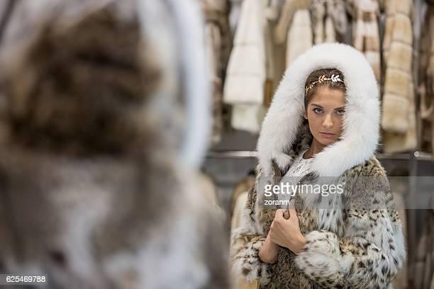 woman trying fur coat in store - 毛皮のコート ストックフォトと画像