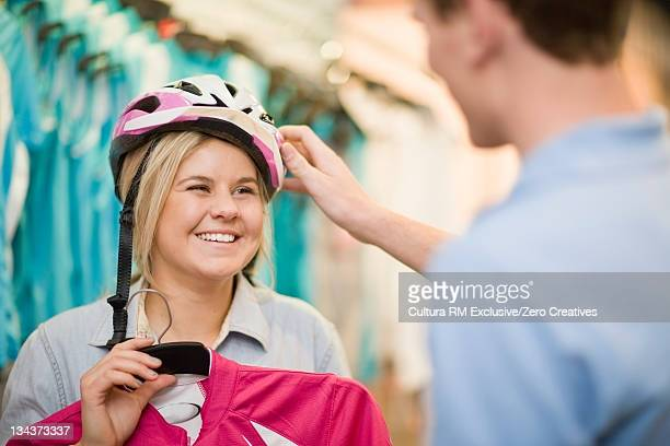 Woman trying on bicycle helmet in shop