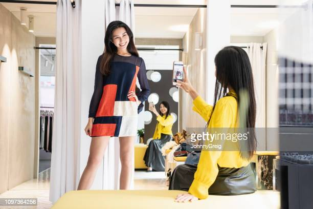 woman trying on clothes and friend photographing - fitting room stock pictures, royalty-free photos & images