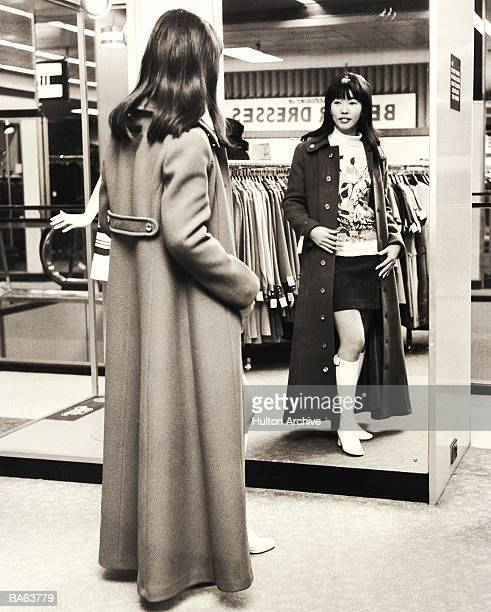 Woman trying on coat in shop, looking in mirror (B&W)