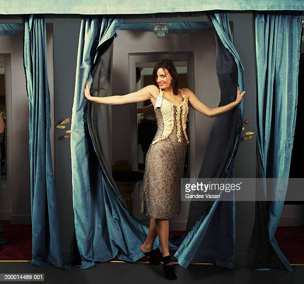 woman trying on dress in changing room, smiling, portrait - fitting room stock pictures, royalty-free photos & images