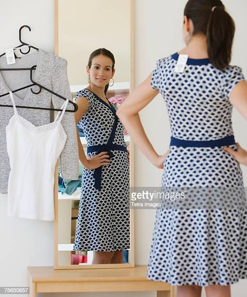 Woman trying on dress in clothing store