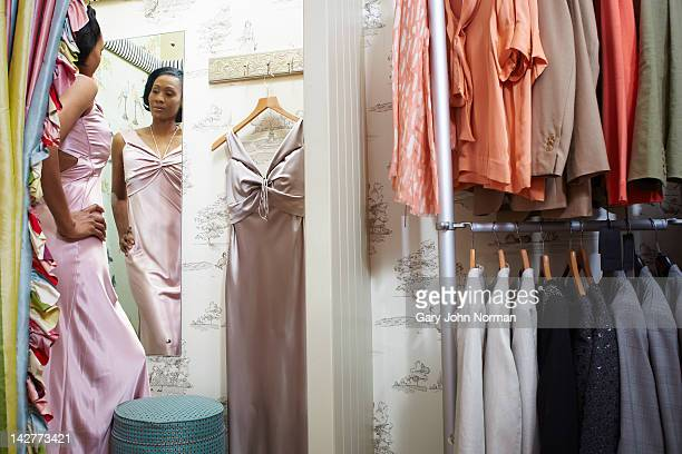 woman trying on dresses in boutique shop - dress stock pictures, royalty-free photos & images
