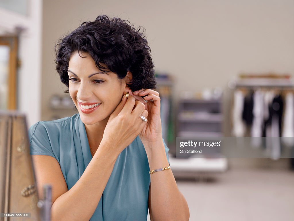 Woman trying on earrings in store : Stock Photo