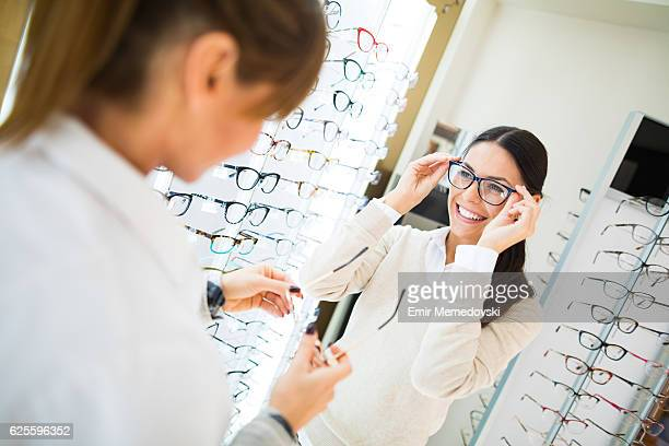 woman trying on eyeglasses in optical shop - occhiali da vista foto e immagini stock