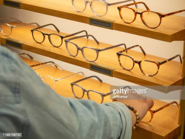 woman trying on eyeglasses - optometry stock pictures, royalty-free photos & images