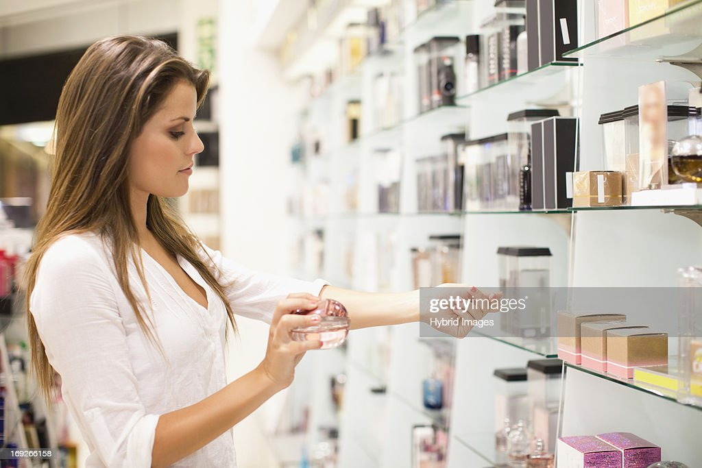 Woman trying on fragrances in store : Stock Photo