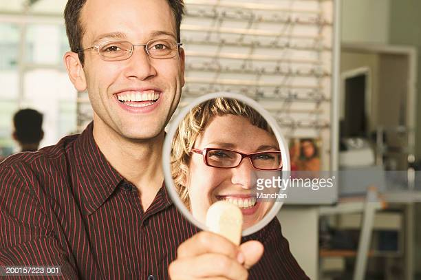Woman trying on glasses in front of mirror held by man, portrait