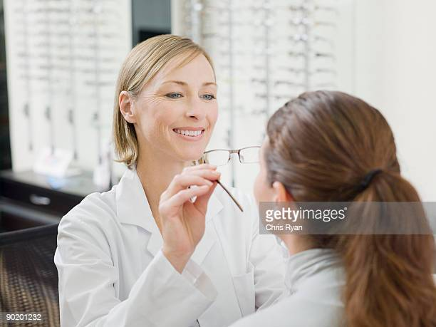 woman trying on glasses in optometrists shop - optometry stock pictures, royalty-free photos & images
