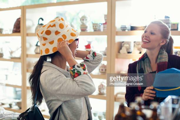 Woman trying on hat while shopping with friend