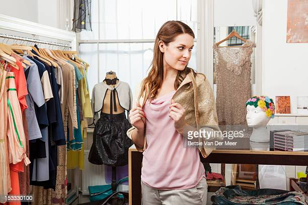 Woman trying on jacket in designer shop.
