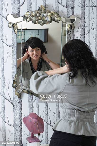 Woman trying on necklace in front of mirror in retail store, rear view