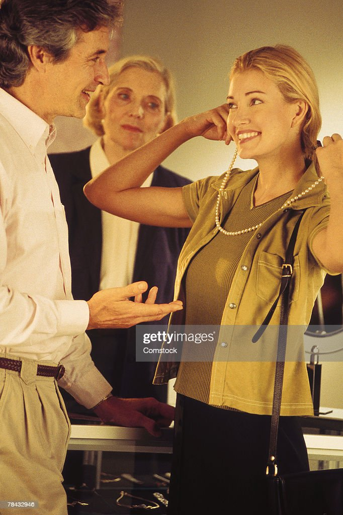 Woman trying on necklace with man and woman looking on : Stockfoto