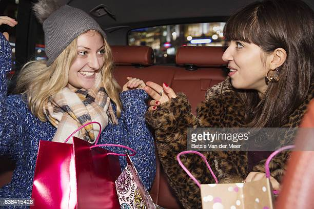 Woman trying on new hat, friend admiring it, sitting in back of car.