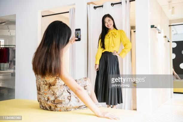 femme essayant sur la tenue avec l'ami photographiant - jupe photos et images de collection