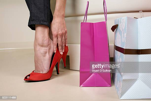 woman trying on red shoes - foot fetishes stock pictures, royalty-free photos & images
