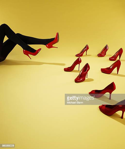 woman trying on red shoes - footwear stock pictures, royalty-free photos & images