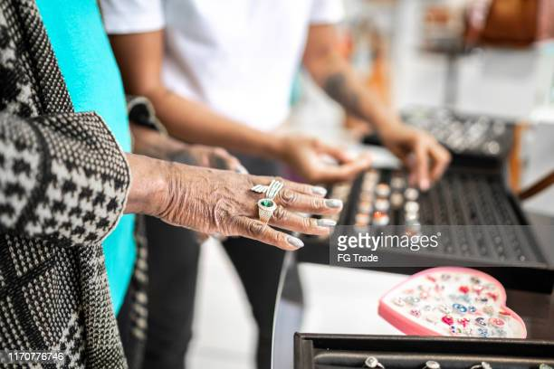 woman trying on rings at jewelry store - rhinestone stock pictures, royalty-free photos & images