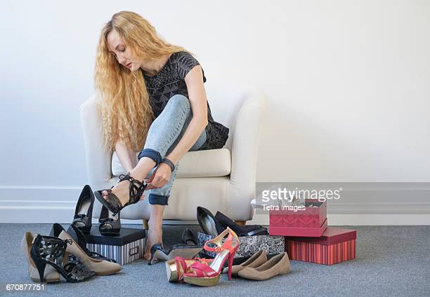 Woman trying on shoes sitting on white armchair