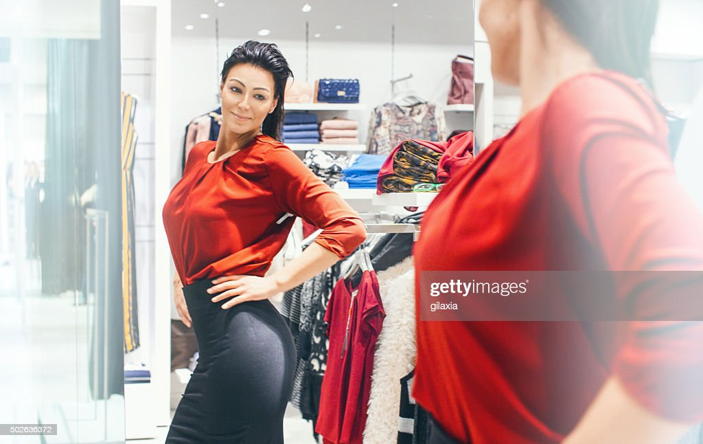 Woman trying on some clothes at a retail store. : Stock Photo