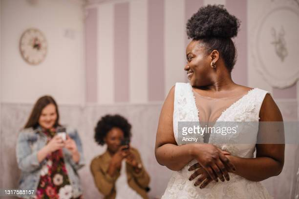 woman trying on wedding dress with female friends having fun and taking photographs. - wedding dress stock pictures, royalty-free photos & images