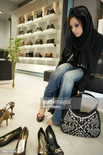 a woman trying shoes at a shop in a mall, dubai, uae. - arab feet photos et images de collection