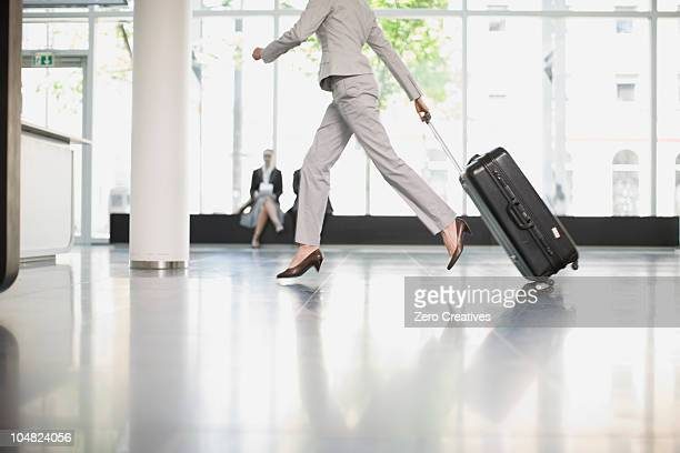 woman trying to catch her flight - wheeled luggage stock photos and pictures